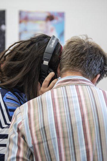 Zwei Menschen hören etwas über Kopfhörer
